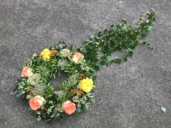 Věnec z oranžových a žlutých růží s vlečkou z břečťanu